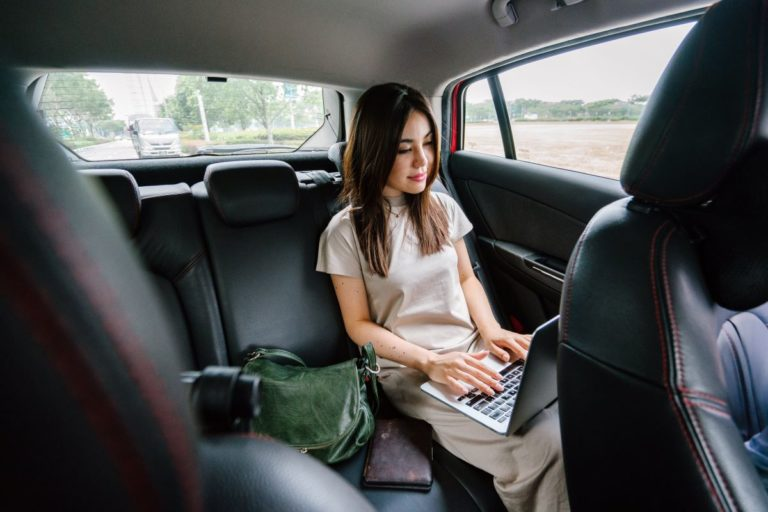 woman working on laptop while inside a car