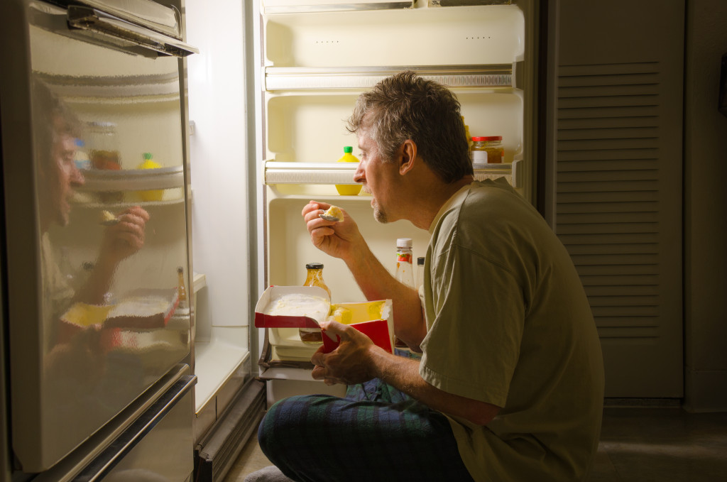 man eating near a refrigerator