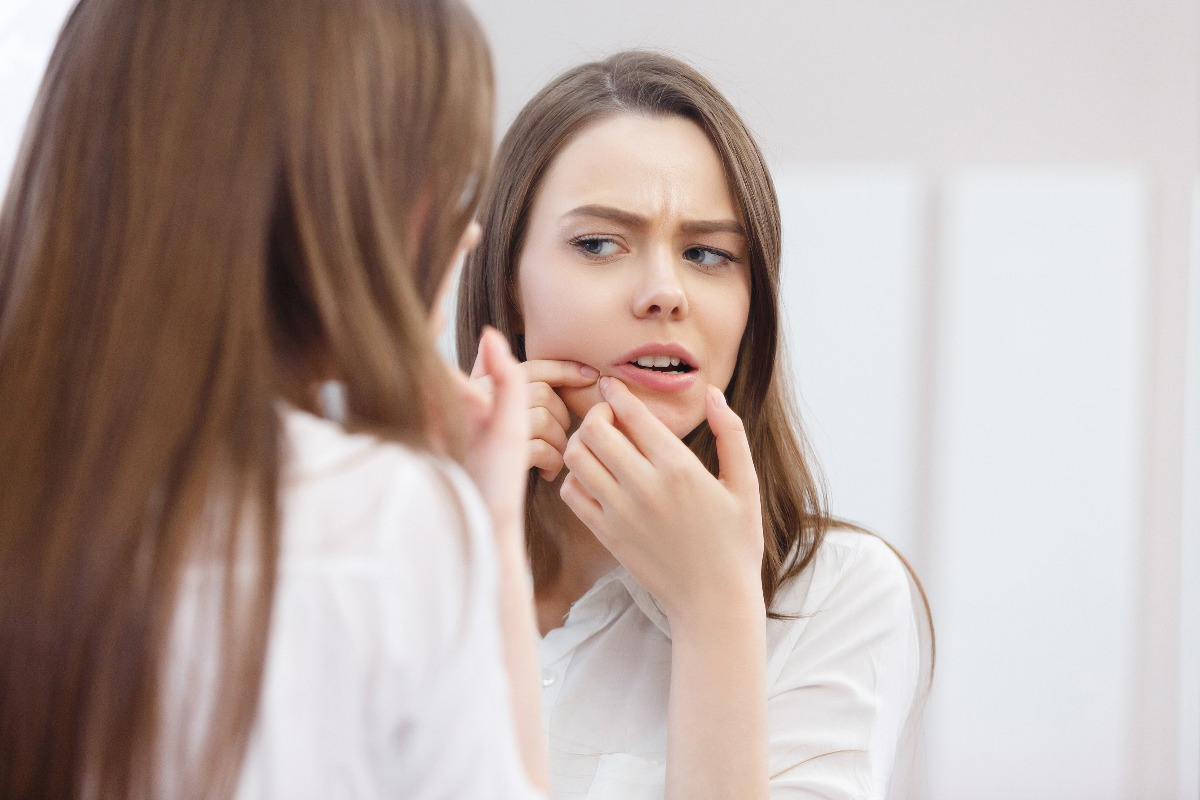 woman tending to her pimple