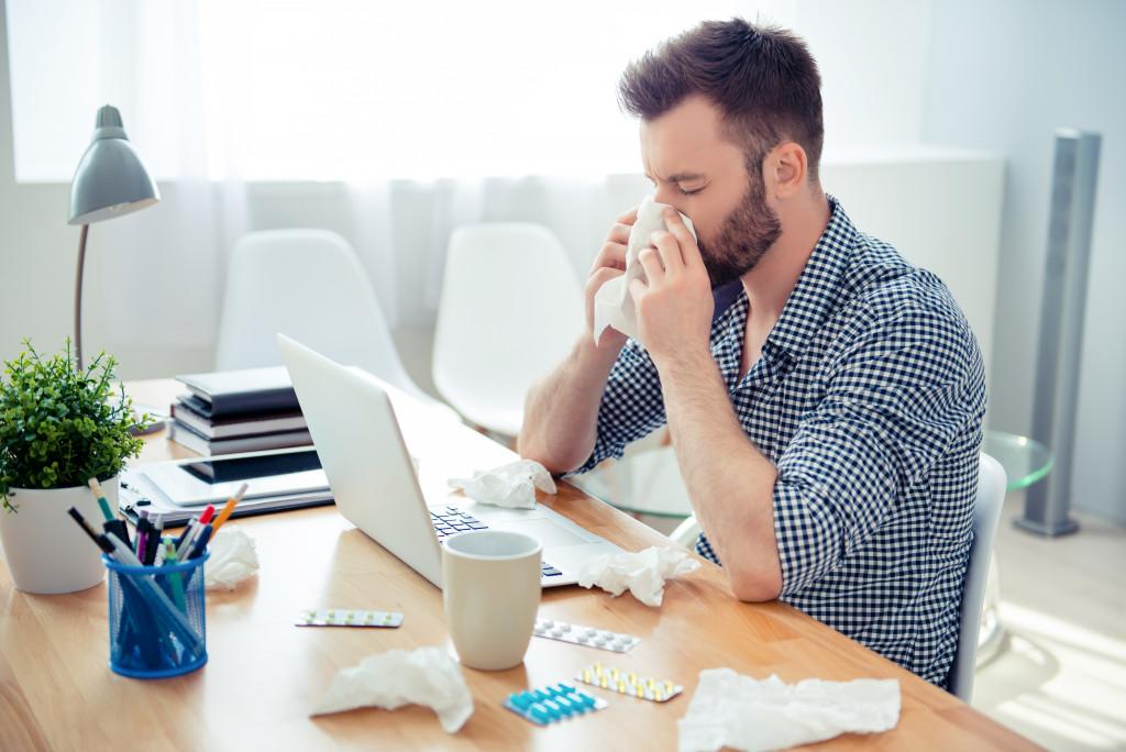man having allergic reaction while working