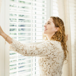 woman opening window blinds